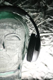 Half Headphones from front. Half front view of headphones on glass head Stock Photography