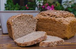 Half of homemade black bread with some bread slices on brown background Stock Image