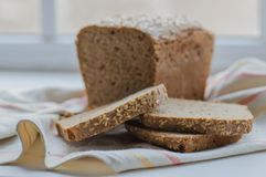 Half of homemade black bread with some slices on linen towel Royalty Free Stock Images