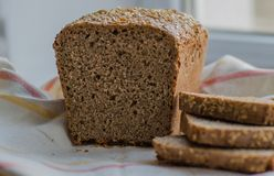 Half of homemade black bread with some slices on linen towel Stock Image