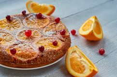 A half of homemade orange cake decorated with fresh red cranberries and orange slices on the gray background. Citrus pie. Flat lay. Side view Royalty Free Stock Photos