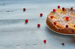 A half of homemade orange cake with fresh red cranberries on the gray background with free copy space on the left side. Citrus pie. Flat lay. Side view Stock Images