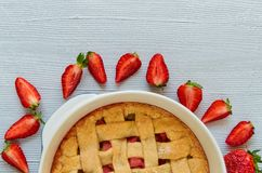 A half of homemade rhubarb strawberry pie in the baking dish on the gray kitchen table with copy space. Vegetarian pie. Decorated with organic sliced Royalty Free Stock Photos