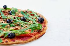 A half of homemade vegetarian pizza isolated with fresh rucola, tomatoes, black olives on the white table close up. Veggie fast food on the white background Stock Image
