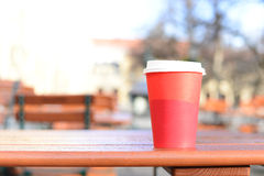 A half of hot coffee in red paper cup on wooden table in outdoor. Park Stock Photo