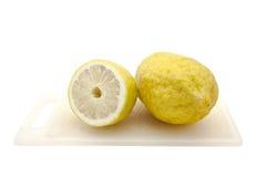 Half Japanse citroen op scherpe geïsoleerdel raad met mes, Royalty-vrije Stock Foto's