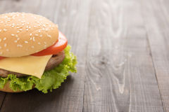 Half Juicy cheeseburger on the wooden background. Stock Images
