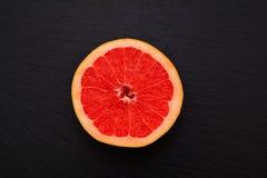 Half of juicy ripe grapfruit on black slate board, plate, tray. Citrus fruit fresh royalty free stock images