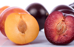Half juicy yellow and cherry plums. Closeup Royalty Free Stock Photos