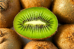 Half kiwi in the middle of other kiwis. Lying on the white surface stock photo