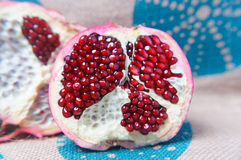 Half a large red pomegranate. On linen the tablecloth royalty free stock photography