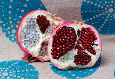 Half a large red pomegranate. On linen the tablecloth royalty free stock photo