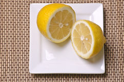 Half lemon. Fresh lemon cut in half on a plate Stock Photography