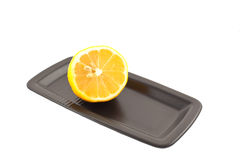 Half of lemon on a black square plate. Isolated on a white background royalty free stock photos