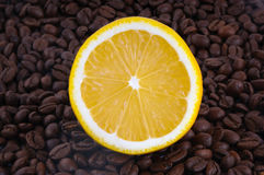 Half a lemon and coffee beans. Half a yellow  lemon and brown coffee beans Royalty Free Stock Photos