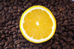 Half a lemon and coffee beans. Half a yellow  lemon and brown coffee beans Royalty Free Stock Photography