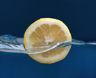 Half lemon drop. Over water wave on blue background Royalty Free Stock Image