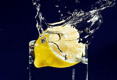 Half of lemon falling down in glass Royalty Free Stock Photography