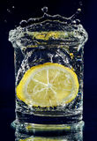 Half of lemon falling down in glass with water Stock Photo