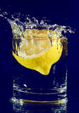 Half of lemon falling down in glass with water Royalty Free Stock Photos