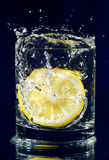 Half of lemon falling down in water Stock Images