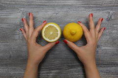 Half a lemon in the left hand and whole lemon in the right hand Stock Photos