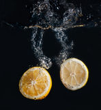 Half lemon and orange in water splash Royalty Free Stock Photography