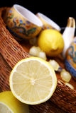 Half of lemon with reflection. Near tea cups and basket Royalty Free Stock Images
