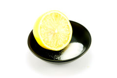 Half a Lemon and Salt. Half a juicy yellow lemon in a small black dish with salt on a white background Stock Images