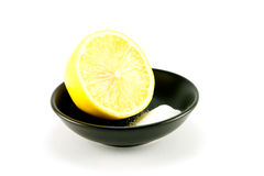 Half a Lemon and Salt. Half a juicy yellow lemon in a small black dish with salt on a white background Stock Photo