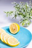 Half a lemon and slices on a blue plate stock images
