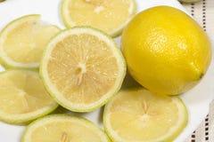Half lemon and slices beside a full lemon in white dish Royalty Free Stock Images