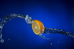 Half of lemon and splash of water on blue background. Half of lemon and splash of water on blue background Royalty Free Stock Image