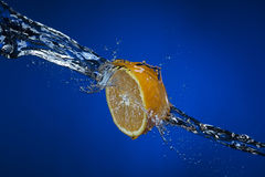 Half of lemon and splash of water on blue background. Half of lemon and splash of water on blue background Stock Images