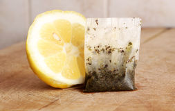 Half lemon and a tea bag. A detailed view of half a lemon and a tea bag, on a wooden cutting board, inside a kitchen with tiles, landscape cut stock photography