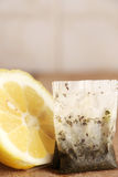 Half lemon and a tea bag. A detailed view of half a lemon and a tea bag, on a wooden cutting board, inside a kitchen with tiles, portrait cut Royalty Free Stock Photography
