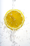 Half lemon wash. Cut lemon suspended in mid-air with water splashing around it Royalty Free Stock Photography