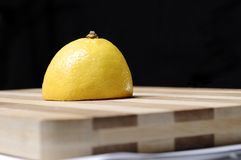 Half of lemon on wood kitchen board Stock Images