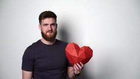 Half lengteportret van de jonge gebaarde hipstermens die rode hartvorm houden stock videobeelden