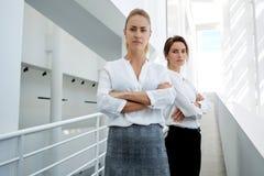 Half lengteportret van een succesvolle onderneemster wat eerst willen stellen terwijl haar partner die zich aan de kant bevinden, Stock Foto's