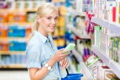 Half lengteportret van meisje bij de winkel die schoonheidsmiddelen kiezen Stock Foto's