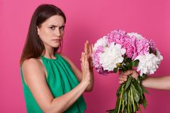 Half length of lady dressed green sundress, refuses beautiful bouquet of white and pink peony flowers from faceless person on. Yellow studio background stock photos