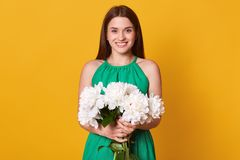 Half length of lady in elegant green dress keeps beautiful bouquet of flowers in hands on yellow studio background, being happy to. Recive peonies as presenmt royalty free stock photos