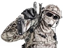 Special Forces Operator. Half length low angle studio shot of special forces soldier in field uniforms and face mask with sniper rifle on his shoulder, portrait stock image
