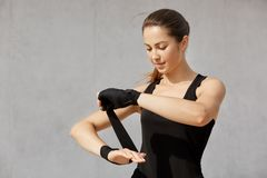 Half length photo of brunette sporty woman with ponytail, wearing black outfit, wrapping wrist bandage, standing against gray royalty free stock photo