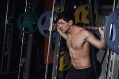 Half length portrait of athletic man doing squats working out with barbell. Royalty Free Stock Photo