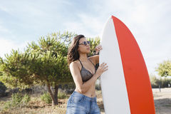 Half length portrait of an attractive brunette hair model posing with her surfboard in the fresh air in sunny day, Stock Photography