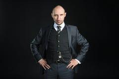Half-length portrait of bald businessman wearing business suit Stock Image