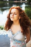Girl with closed eyes. Half-length portrait of a beautiful red-headed girl with closed eyes standing near the lake stock photos