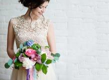 Half length portrait of brunette smiling woman dressed in sleeveless light evening dress.  Royalty Free Stock Image